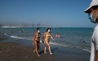 TOPSHOT - People wearing face masks walk along La Misericordia Beach in Malaga on July 22, 2020. - The world's second-most popular destination after France, Spain was badly hit by the coronavirus that has claimed more than 28,400 lives and dealt a major blow to its tourism industry, which accounts for 12 percent of GDP. (Photo by JORGE GUERRERO / AFP) (Photo by JORGE GUERRERO/AFP via Getty Images)