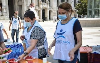 Un momento della distribuzione di anguria fresca e bottigliette d acqua ai senzatetto dai volontari del Progetto Arca in piazza duca d aosta all'esterno della stazione Centrale, Milano, 14 Agosto 2020. ANSA/MATTEO CORNER
