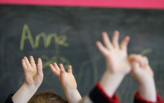 GLASGOW, SCOTLAND - JANUARY 28: Children wave their hands at a private nursery school January 28, 2005 in Glasgow, Scotland. The average price of pre-school care has increased over the past year, sending child care prices to an average of GBP200 in parts of the southeast. Many working parents in the UK have called for pre-school childcare subsidies such as those in France where nearly 100% of three-year-olds are in pre-school education, despite the fact that school attendance is not compulsory until they turn five. (Photo by Christopher Furlong/Getty Images)