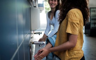 Two highschool students wash their hands prior to attend class at the Lycee Laperousse school, in Noumea, on the French Pacific island of New Caledonia, on April 22, 2020 on the opening day of the schools following a for weeks lockdown installed by the government to curb the spread of the COVID-19, (the novel coronavirus). (Photo by Theo Rouby / AFP) (Photo by THEO ROUBY/AFP via Getty Images)