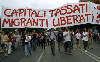 """GEN14-20010719-GENOA, ITALY: Demonstrators carry a placard reading """"Capitali tassati, Migranti liberati"""" (Put taxes on the capital, free the immigrants) as about 25 000 people protest in the center of Genua against the G8 (Group of Eight) summit, Thursday 19 July 2001, a day before the start of the conference. Heads of state and government of the G8 countries will meet here 20 to 22 July amid heightened security to deal with an expected 120,000 anti-globalisation demonstrators. EPA PHOTO EPA/ANJA NIEDRINGHAUS/hh"""