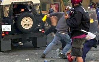 Una delle fotografie messe in rete sul sito di Radio Sherwood, in cui si vede Carlo Giuliani (in basso a destra, parzialmente coperto da un altro manifestante) che raccoglie da terra un estintore il 21 luglio 2001. Dalla camionetta dei carabinieri spunta ua pistola. ANSA / RADIO SHERWOOD