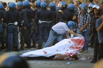 392176 21: Police cover the body of Carlo Giuliani , a demonstrator they shot to death during protests in central Genoa, July 20, 2001. Approximately 600 violent protesters fought with police, torched cars and looted shops throughout the day as Group of Eight leaders arrived at a heavily guarded palace for their summit. (Photo by Sean Gallup/Getty Images)