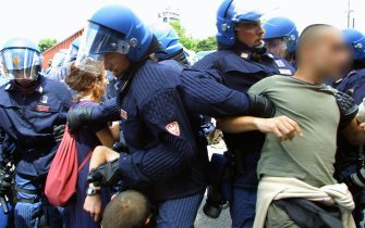 """GEN18-20010720-GENOA, ITALY: Police struggle with demonstrators, Friday 20 July 2001, as anti-globalisation protesters demonstrate in Genoa. Hardline demonstrators have vowed to try to break into the high-security """"red zone"""" surrounding the Palazzo Ducale, where the leaders of the G8 (Group of Eight) started their three-day annual summit Friday. EPA PHOTO/ANJA NIEDRINGHAUS/hh"""