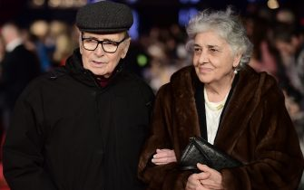 Italian composer Ennio Morricone poses with his wife Maria Travia on the red carpet of the European premiere of film 'The Hateful Eight' in London on December 10, 2015.  AFP PHOTO / LEON NEAL (Photo by LEON NEAL / AFP)        (Photo credit should read LEON NEAL/AFP via Getty Images)