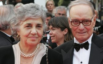 Cannes, FRANCE: Italian composer Ennio Morricone (R) and his wife Maria Travia pose 25 May 2007 upon arriving at the Festival Palace in Cannes, southern France, for the premiere of US director James Gray's film 'We Own the Night' during the 60th edition of the Cannes Film Festival. The film is in competition for the Palme d'Or prize. The Cannes festival unspooled some of its last films Friday as it prepared for its weekend climax -- an awards night that will reward one of 22 competition films with the prestigious Palme d'Or.         AFP PHOTO / FRANCOIS GUILLOT (Photo credit should read FRANCOIS GUILLOT/AFP via Getty Images)