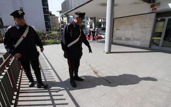 Carabinieri nei pressi dell'ufficio postale di Aversa, in provincia di Caserta, dove nella notte una rissa per futili motivi ha provocato la morte per accoltellamento di un ragazzo di 15 anni, Emanuele Di Caterino, nipote di Gaetano Iorio, esponente del clan Schiavone, sottoposto a sorveglianza speciale, 8 aprile 2013. Il ragazzo è morto nella notte in ospedale mentre l'accoltellatore, di 17 anni, è stato arrestato. Entrambi erano incensurati. Carabineers near the post office of Aversa (Caserta, Italy), where tonight a 15 years old boy, Emanuele Di Caterino, was knifed to death after a fight with a 17 years old boy, both uncensured. The dead boy is the nephew of Gaetano Iorio, a representative of Schiavone camorra clan, 8 April 2013.ANSA/ CESARE ABBATE