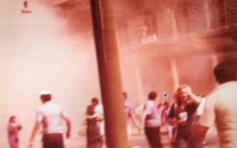 Una foto che ritrae il piazzale della stazione di Bologna la mattina del 2 agosto 1980, poco dopo l'esplosione che causÚ 85 morti e 200 feriti. L'immagine inedita, a colori, Ë stata ritrovata dall'avvocato Andrea Speranzoni, difensore dell'associazione dei familiari delle vittime della Strage. Si vedono tra l'altro una donna che sembra allontanarsi andando incontro all'obiettivo, con una borsa sulla spalla destra e l'altra mano sulla tempia, un vigile urbano di spalle e altre persone in secondo piano, mentre sullo sfondo il fumo ha invaso l'ingresso della stazione e si Ë propagato all'esterno, fino ad arrivare pi˘ in alto del tetto.ANSA