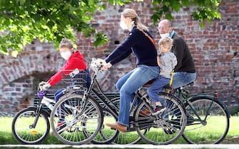 """Una famiglia  in bicicletta al parco Sempione di Milano  nel primo giorno della """"Fase2"""" determinata dall'emergenza del Coronavirus. Milano 4 Maggio 2020. ANSA / MATTEO BAZZI"""