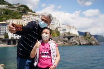 AMALFI, ITALY - JUNE 02: A grandfather with his niece taking a selfie at Amalfi's port  on June 02, 2020 in Amalfi, Italy. Many Italian businesses have been allowed to reopen, after more than two months of a nationwide lockdown meant to curb the spread of Covid-19. (Photo by Francesco Pecoraro/Getty Images)