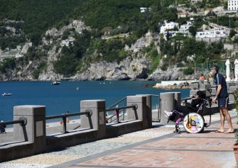 SALERNO, ITALY - JUNE 02: Disabled girl with her companion taking a walk on Vietri sul Mare seafront on June 02, 2020 in Salerno, Italy. Many Italian businesses have been allowed to reopen, after more than two months of a nationwide lockdown meant to curb the spread of Covid-19. (Photo by Francesco Pecoraro/Getty Images)