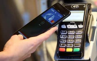 Apple Pay il metodo di pagamento elettronico ideato dall'azienda di Cupertino.  E' un sistema collegato direttamente alla carte elettroniche. Funziona avvicinando l'iPhone o l'Apple Watch al POS dei negozi che accettano pagamenti contactless (tenendo premuto il sensore Touch ID) Milano, 16  Maggio 2017. ANSA / MATTEO BAZZI
