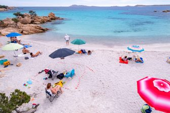 PORTO CERVO, ITALY - JUNE 07: Some tourists on a beach in Sardinia try to respect the rules of social distancing by using a white and red ribbon to mark their space on the beach on the first weekend of phase 3 after the lockdown due to Covid-19 on June 07, 2020 in Porto Cervo, Sardegna, Italy. Many Italian businesses have been allowed to reopen, after more than two months of a nationwide lockdown meant to curb the spread of Covid-19. (Photo by Emanuele Perrone/Getty Images)