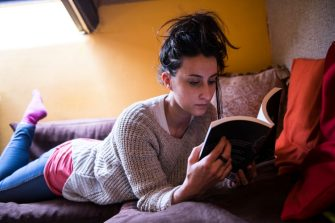 TURIN, ITALY - MARCH 15: A woman reads a book at home to pass the time after the Italian government clamped down on public events, closed bars, restaurants and schools, imposed travel restrictions and advised citizens to stay at home in an attempt to slow the spread of the Coronavirus on March 15, 2020 in Turin, Italy. Italy has been the worst hit county outside of China, with over 24,747 confirmed cases of COVID-19 and as many as 1,809 fatalities. (Photo by Stefano Guidi/Getty Images)
