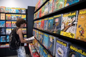 A woman reads a comics book in a shop during the official opening of the comics hero Spirou Provence Park in Monteux, southern France, on June 1, 2018. (Photo by BERTRAND LANGLOIS / AFP)        (Photo credit should read BERTRAND LANGLOIS/AFP via Getty Images)