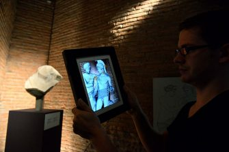 """A visitor holds a tablet showing a statue of Mars and Venus at the Trajan's Market (Mercati di Traiano) museum on September 23, 2014 in Rome, where the exhibition """"The keys of Rome. The city of Augustus"""" runs till May 10, 2015. """"Keys To Rome"""" is an international exhibition on the city of Augustus and the Roman Empire organized in four locations (Rome, Alexandria, Amsterdam, and Sarajevo) by the European network of Virtual Museums, V-MUST, coordinated by the Italian National Council of Researches.  AFP PHOTO / VINCENZO PINTO        (Photo credit should read VINCENZO PINTO/AFP via Getty Images)"""