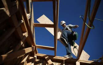 PETALUMA, CA - JANUARY 21:  A worker carries lumber as he builds a new home on January 21, 2015 in Petaluma, California. According to a Commerce Department report, construction of new homes increased 4.4 percent in December, pushing building of new homes to the highest level in nine years.(Photo by Justin Sullivan/Getty Images)