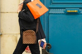 PARIS, FRANCE - JUNE 15: A passerby wears a black jacket, a brown Vuitton checkered bag, holds an orange paper shopping bag from Le Bon Marche, on June 15, 2020 in Paris, France. (Photo by Edward Berthelot/Getty Images)
