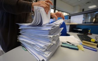 An employee goes through documents in a tax office on November 7, 2012 in Rome.  AFP PHOTO / ANDREAS SOLARO        (Photo credit should read ANDREAS SOLARO,ANDREAS SOLARO/AFP via Getty Images)