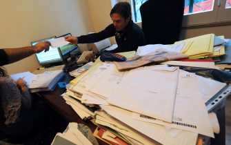 An accountant checks tax forms of one of his clients in his office in Naples on October 22, 2012.  AFP PHOTO / MARIO LAPORTA        (Photo credit should read MARIO LAPORTA/AFP via Getty Images)
