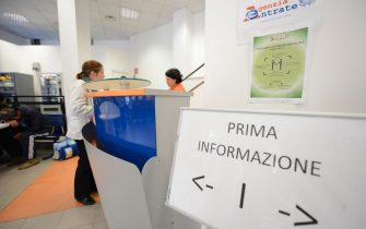 A woman speaks to an employee at an information desk in a tax office on November 7, 2012 in Rome.  AFP PHOTO / ANDREAS SOLARO        (Photo credit should read ANDREAS SOLARO,ANDREAS SOLARO/AFP via Getty Images)