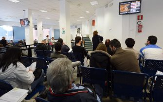 People wait for their turn in a tax office on November 7, 2012 in Rome.  AFP PHOTO / ANDREAS SOLARO        (Photo credit should read ANDREAS SOLARO,ANDREAS SOLARO/AFP via Getty Images)