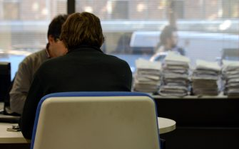 A man speaks with an employee in a tax office on November 7, 2012 in Rome.  AFP PHOTO / ANDREAS SOLARO        (Photo credit should read ANDREAS SOLARO,ANDREAS SOLARO/AFP via Getty Images)