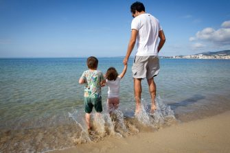 A father plays with his children on the Portixol Beach in Palma de Mallorca, on April 26, 2020 during a national lockdown to prevent the spread of the COVID-19 disease. - After six weeks stuck at home, Spain's children were being allowed out today to run, play or go for a walk as the government eased one of the world's toughest coronavirus lockdowns. Spain is one of the hardest hit countries, with a death toll running a more than 23,000 to put it behind only the United States and Italy despite stringent restrictions imposed from March 14, including keeping all children indoors. Today, with their scooters, tricycles or in prams, the children accompanied by their parents came out onto largely deserted streets. (Photo by JAIME REINA / AFP) (Photo by JAIME REINA/AFP via Getty Images)