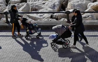 Due mamme con i passeggini camminano sul lungomare Caracciolo di Napoli, 7 febbraio 2019. ANSA / CIRO FUSCO