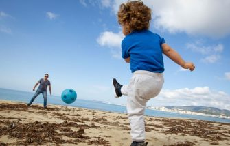 TOPSHOT - A child plays footbal with his father at Can Pere Antoni Beach in Palma de Mallorca, on April 26, 2020 during a national lockdown to prevent the spread of the COVID-19 disease. - After six weeks stuck at home, Spain's children were being allowed out today to run, play or go for a walk as the government eased one of the world's toughest coronavirus lockdowns. Spain is one of the hardest hit countries, with a death toll running a more than 23,000 to put it behind only the United States and Italy despite stringent restrictions imposed from March 14, including keeping all children indoors. Today, with their scooters, tricycles or in prams, the children accompanied by their parents came out onto largely deserted streets. (Photo by JAIME REINA / AFP) (Photo by JAIME REINA/AFP via Getty Images)