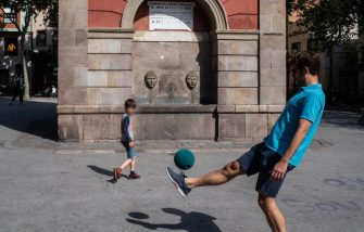 BARCELONA, SPAIN - APRIL 26: A father and his son play football at Plaça de la Vila de Gracia on April 26, 2020 in Barcelona, Spain. Children in Spain, which has had one of the stricter lockdowns in Europe, are now allowed to leave their homes for up to an hour per day. The country has had more than 220,000 confirmed cases of COVID-19 and over 20,000 reported deaths, although the rate has declined after weeks of quarantine measures. (Photo by David Ramos/Getty Images)