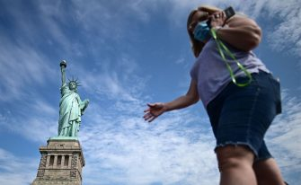 Tourists wearing facemasks walk on the reopened Liberty Island in front of the Statue of Liberty on July 20, 2020  in New York City. - Just a few tourists visited the reopened monument as New York City moves into Phase 4 of the Coronavirus lockdown. (Photo by Johannes EISELE / AFP) (Photo by JOHANNES EISELE/AFP via Getty Images)
