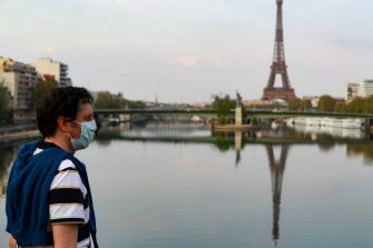 A man wearing a protective facemask looks at the reflection of the Eiffeil Tower on the Seine river, in Paris, on April 11, 2020, on the 26th day of a strict lockdown aimed at curbing the spread of the COVID-19 pandemic , caused by the novel coronavirus. (Photo by Ludovic MARIN / AFP) (Photo by LUDOVIC MARIN/AFP via Getty Images)