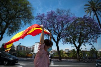 """A demonstrator wearing a face mask waves a Spanish flag during a """"caravan for Spain and its freedom"""" protest by far-right party Vox in Sevilla on May 23, 2020. - Spain, one of the most affected countries in the world by the novel coronavirus with 28,628 fatalities, has extended until June 6 the state of emergency which significantly limits the freedom of movement to fight the epidemic. The left-wing government's management of the crisis has drawn a barrage of criticism from righ-wing parties who have denounced its """"brutal confinement"""". (Photo by CRISTINA QUICLER / AFP) (Photo by CRISTINA QUICLER/AFP via Getty Images)"""