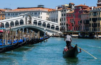A gondolier goes with customers for a gondola ride on the Grand Canal near Rialto Bridge in Venice on June 12, 2020 as the country eases its lockdown aimed at curbing the spread of the COVID-19 infection, caused by the novel coronavirus. (Photo by ANDREA PATTARO / AFP) (Photo by ANDREA PATTARO/AFP via Getty Images)
