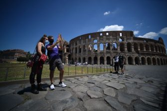 Visitors stand by the Colosseum monument which reopens to the public on June 1, 2020 in Rome, while the country eases its lockdown aimed at curbing the spread of the COVID-19 infection, caused by the novel coronavirus. - The Colosseum monument reopens on June 1, 2020 after having been closed since March 8, 2020, with adequate sanitary protection for staff and visitors, secure routes, compulsory reservations and modified schedules to avoid crowds at peak times. (Photo by Filippo MONTEFORTE / AFP) (Photo by FILIPPO MONTEFORTE/AFP via Getty Images)