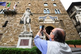FLORENCE, ITALY - MAY 13:  A man takes a photo of a statue on the Piazza della Signoria empty of tourists  on May 13, 2020 in Florence, Italy. (Photo by Roberto Serra - Iguana Press/Getty Images)