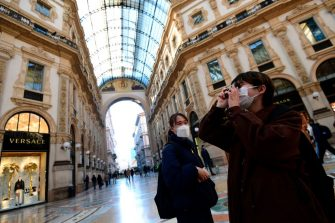 Tourists wearing protective masks take pictures in Galleria Vittorio Emanuele II in the centre of Milan, on February 28, 2020, after COVID-19, the novel coronavirus, spread to Italy. - Italy urged tourists spooked by the new coronavirus on February 28 not to stay away, but efforts to reassure the world it was managing the outbreak were overshadowed by a sharp rise in case numbers. Some 650 people have tested positive for the virus in Italy, though only 303 are considered serious clinical cases, and deaths hit 17 -- by far the highest in Europe -- according to the latest figures from the civil protection agency. (Photo by Miguel MEDINA / AFP) (Photo by MIGUEL MEDINA/AFP via Getty Images)