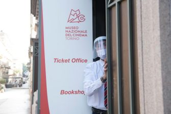 TURIN, ITALY - JUNE 02: Museum guard wears a protective mask while opening the entrance outside the National Cinema Museum on June 2, 2020 in Turin, Italy. The National Cinema Museum of Turin is housed inside the Mole Antonelliana, a symbol of Turin, the Museum develops spiral upwards, on multiple exhibition levels, with extraordinary collections of the history of cinema from its origins to the present day. Many Italian businesses have been allowed to reopen, after more than two months of a nationwide lockdown meant to curb the spread of Covid-19. (Photo by Stefano Guidi/Getty Images)