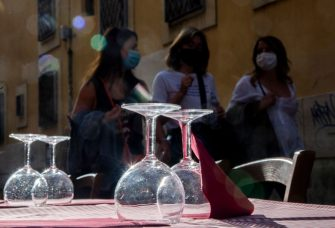 Woman wearing protective face masks walk past a terrace of a restaurant in Trastevere in central Rome on June 5, 2020, as bars and restaurants reopened after months-long closures aimed at stemming the spread of the COVID-19 pandemic, caused by the novel coronavirus. (Photo by Tiziana FABI / AFP) (Photo by TIZIANA FABI/AFP via Getty Images)