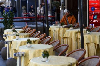 A man wearing a protective mask sits in an empty bar near Piazza del Duomo in the centre of Milan, on February 28, 2020, after COVID-19, the novel coronavirus, spread to Italy. - Italy urged tourists spooked by the new coronavirus on February 28 not to stay away, but efforts to reassure the world it was managing the outbreak were overshadowed by a sharp rise in case numbers. Some 650 people have tested positive for the virus in Italy, though only 303 are considered serious clinical cases, and deaths hit 17 -- by far the highest in Europe -- according to the latest figures from the civil protection agency. (Photo by Miguel MEDINA / AFP) (Photo by MIGUEL MEDINA/AFP via Getty Images)
