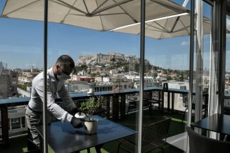 A waiter prepares tables in a roof cafe of an hotel central Athens on June 1, 2020, as Greece eases coronavirus measures and reopening some of the hotels , priomary schools and nurseries. - Greece on May 30, 2020 expanded its list of approved flights from EU destinations to include airports in countries hard-hit by the coronavirus, but flights from the worst-hit regions will still be subject to quarantine measures. (Photo by Louisa GOULIAMAKI / AFP) (Photo by LOUISA GOULIAMAKI/AFP via Getty Images)