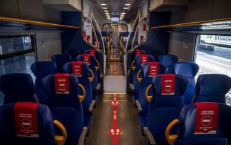 """ROME, ITALY - MAY 04: A general view on a train shows the stickers on the seats reading """"Leave this seat free"""" at the Termini Central train Station during the first day of the so called phase two due to the Coronavirus (Covid-19) pandemic, on May 4, 2020 in Rome, Italy. Italy was the first country to impose a nationwide lockdown to stem the transmission of the Coronavirus (Covid-19), and its restaurants, theaters and many other businesses remain closed. (Photo by Antonio Masiello/Getty Images)"""