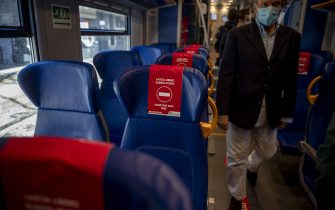"""ROME, ITALY - MAY 04: A general view shows the stickers on the seats reading """"Leave this seat free"""" as a man enters in a train at the Termini Central train Station during the first day of the so called phase two due to the Coronavirus (Covid-19) pandemic, on May 4, 2020 in Rome, Italy. Italy was the first country to impose a nationwide lockdown to stem the transmission of the Coronavirus (Covid-19), and its restaurants, theaters and many other businesses remain closed. (Photo by Antonio Masiello/Getty Images)"""