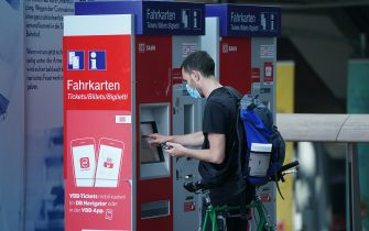 BERLIN, GERMANY - JULY 07: A traveler wearing a protective face mask buys a train ticket at Hauptbahnhof main railway station during the coronavirus pandemic on July 07, 2020 in Berlin, Germany. German state rail carrier Deutsche Bahn is offering disinfectant and is distributing free protective face masks in an effort to encourage people to resume travel following the easing of lockdown measures in Germany. (Photo by Sean Gallup/Getty Images)