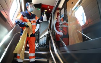 An employee of a cleaning services company disinfect wagons of a TGV high-speed train at a maintenance workshop of the SNCF railway company in Chatillon, on May 14, 2020, as the lockdown introduced two month ago to fight the spread of the Covid-19 diseased caused by the novel coronavirus starts to ease. (Photo by Ludovic MARIN / AFP) (Photo by LUDOVIC MARIN/AFP via Getty Images)