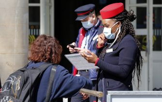 """PARIS, FRANCE - MAY 14: An employee of the SNCF (French state-owned railway company) wearing a protective face mask checks the commuters at the entrance of the """"Gare de l'est"""" railway station as France is slowly reopening after almost two months of strict lockdown throughout the country due to the epidemic of coronavirus (COVID 19) on May 14, 2020 in Paris, France. The Coronavirus (COVID-19) pandemic has spread to many countries across the world, claiming over 300,000 lives and infecting over 4.4 million people. (Photo by Chesnot/Getty Images)"""