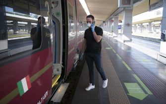 TURIN, ITALY - JUNE 03: A traveler wearing a protective mask enters the train at the Porta Nuova railway station on June 03, 2020 in Turin, Italy. Today 3 June the Italian government has reopened the regional borders thus giving Italians the opportunity to move between the regions again and be able to go to relatives and go on holiday within the Italian borders. Many Italian businesses have been allowed to reopen, after more than two months of a nationwide lockdown meant to curb the spread of Covid-19. (Photo by Stefano Guidi/Getty Images)