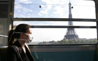 PARIS, FRANCE - APRIL 24: A passenger wearing a protective face mask is seen in a subway train as she passes in front the Eiffel Tower as the lockdown continues due to the coronavirus outbreak (COVID 19) on April 24, 2020 in Paris, France. After a meeting between the Head of State Emmanuel Macron and the mayors, the Elysee Palace said that the wearing of the mask will probably be compulsory in public transport, starting on May 11. The Coronavirus (COVID-19) pandemic has spread to many countries across the world, claiming over 191,000 lives and infecting over 2.7 million people. (Photo by Chesnot/Getty Images)