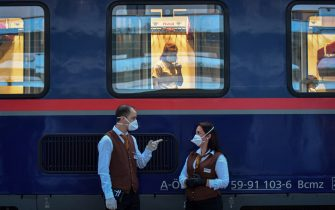 A Romanian woman is seen speaking on her phone through the window of a train car at a railway station in Timisoara city, western Romania, on May 10, 2020, as Romanian carers are on their way to Vienna. - A first group of Romanian carers left in the evening on May 10 Timisoara for Vienna, putting an end to the anxiety of the families of Austrian dependents that the Coronavirus pandemic has been denied crucial help. Normally, 65,000 carers, 80 percent of the women from Romania and Slovakia, officially work in Austria, where 33,000 people require medical assistance day and night. Pressed by Vienna, the Romanian authorities finally gave the green light to the establishment of a night rail link between these two cities, separated by 525 km. Romania, which to date has recorded more than 15,000 cases of Covid-19, including 961 deaths, will not take the first steps towards easing restriction until Friday. (Photo by Daniel MIHAILESCU / AFP) (Photo by DANIEL MIHAILESCU/AFP via Getty Images)